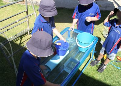 Three students playing with containers filled with water at the school yard